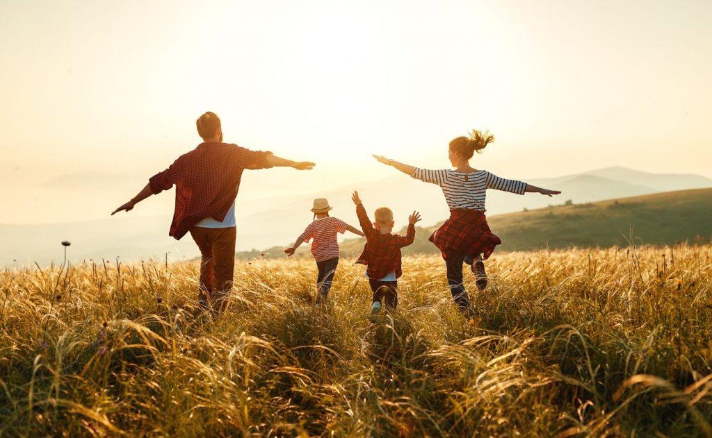 Symbolbild: Familie (Vater, Mutter und zwei Kinder) hüpfen fröhlich über eine Wiese, der untergehenden Sonne entgegen.